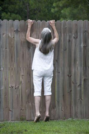 Een nieuwsgierige buur man denkt over hoe ze een kijkje over het hek krijgt.