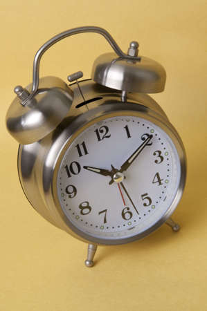 Retro Style Alarm Clock Isolated on a Yellow Background. 版權商用圖片