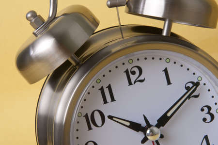 Macro of Retro Silver Alarm Clock Isolated on a Yellow Background.