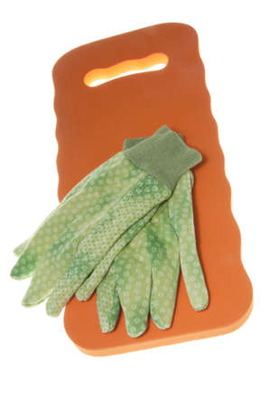 Green polka dot gardening gloves on an orange kneeling pad.  Shot in the studio with focus and lighting emphasis on gloves.