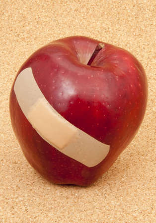 A red apple with a plaster. Symbolic of problems in the education system or fruit industry. Also would work for a problems with health care theme.  Shot in studio on a cork background. photo