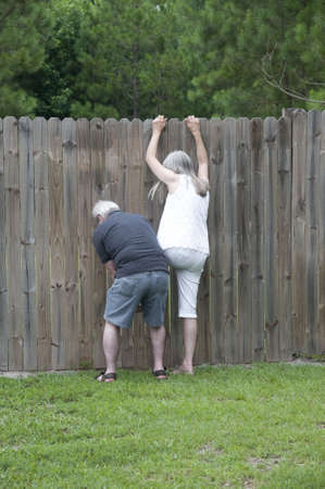 Her husband helps her peek over the fence to see what the neighbors are up to! photo