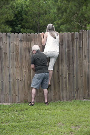 Her husband helps her peek over the fence to see what the neighbors are up to!