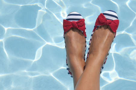 A woman sports some nautical shoes with a pool on a sunny day as the background.  A great shot for summer or 4th of July because of the red, white and blue coloring of the photograph. photo