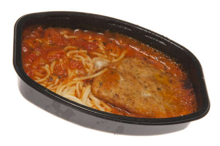 Cooked TV Dinner Chicken and Spaghetti isolated on a white background. You can see the grease, and burned edges from the cooking. Not a gourmet meal! 版權商用圖片