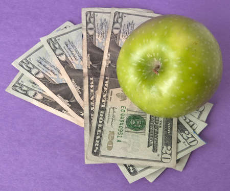 A green apple sits on top of a pile of $20 bills to illustrate the cost of education, food, or health care. photo