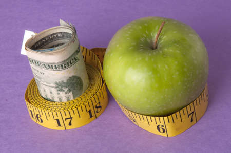 An apple, tape measure, and American currency represents the concept of measuring the cost of healthcare, food, or education.  Can also work for concept of the cost of healthcare, education or food. photo