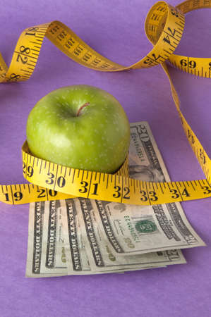 An apple, tape measure, and American currency represents the concept of measuring the cost of healthcare, food, or education.  Can also work for concept of the cost of healthcare, education or food. Reklamní fotografie