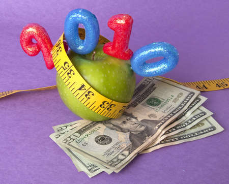 Granny Smith Green Apple with a bright yellow tape measure represents the concepts of the cost of diet and healthy lifestyle. Perhaps this is your New Years Resolution?  Can also work for a high cost of healthcare or education concept. photo