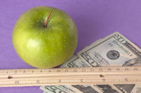 Conceptual image of a bright green apple with a ruler, and American currency on a vibtrant purple background to represent the cost of education. photo