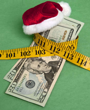 holiday budget: Money squeezed by a measuring tape representing a tight holiday budget.