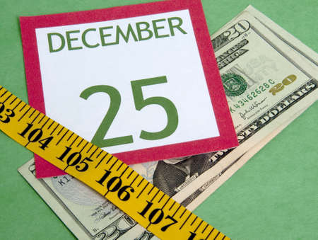 holiday budget: Christmas calendar page squeezed by a measuring tape representing a tight holiday budget. Stock Photo