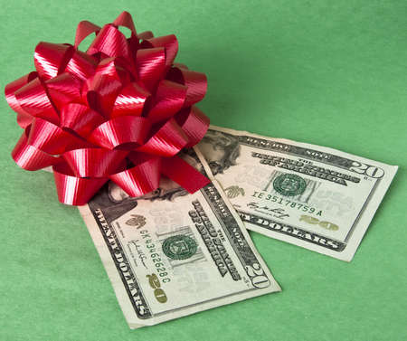 christmas budget: Bow and currency represents the cost of giving gifts during the holidays. Stock Photo