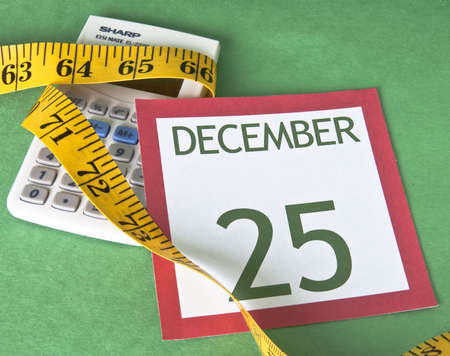 holiday budget: Christmas calendar page with a calculator squeezed by a measuring tape representing a tight holiday budget.
