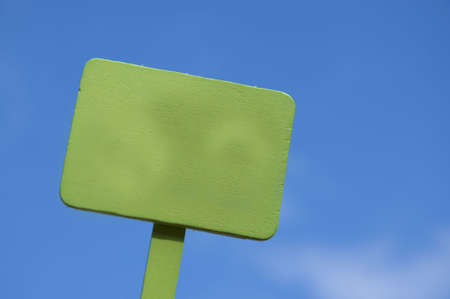 Bright green sign on a blue sky background.  Blank for your message.  Climate Change, Global Warming, Nature, Outdoors, Gardening, Etc. Stock Photo
