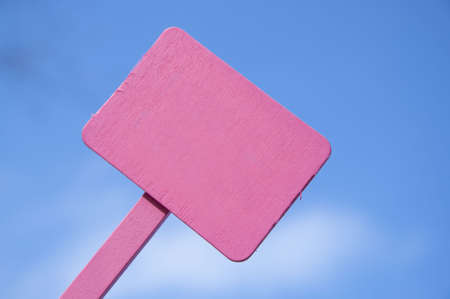 Bright pink sign on a blue sky background.  Blank for your message.  Climate Change, Global Warming, Nature, Outdoors, Gardening, Etc. Stock Photo