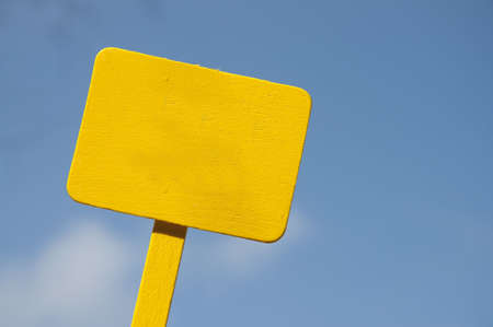 Bright yellow sign on a blue sky background.  Blank for your message.  Climate Change, Global Warming, Nature, Outdoors, Gardening, Etc. Stock Photo