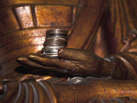 buddha image: Close up image of coins in the hand of a buddha statue.
