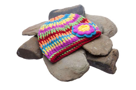 Brightly colored hat sits on a pile of smooth rover rocks. Isolated on a white background with a clipping path. Stock Photo - 6398577