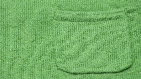 Close up image of the pocket on a green wool sweater.