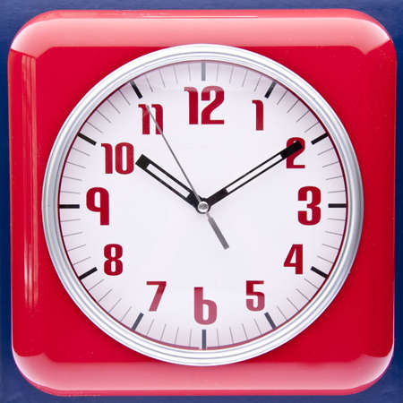 navy blue background: Retro revival red wall clock on a navy blue background.