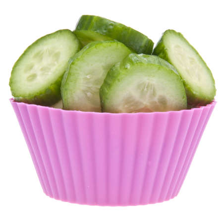 Pink cupcake wrapper filled with fresh cucumber slices for a diet themed image.  Isolated on white with a clipping path. Stock Photo - 6466865