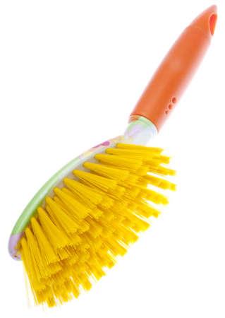 Moderne kijk op de voorjaarsschoonmaak met deze feloranje en gele reinigingsborstel. Stockfoto