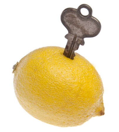 broken home: Key with lemon symbolizes a car or house that is a lemon - something you think is good; but turns out to be broken.; Isolated on white with clipping path.