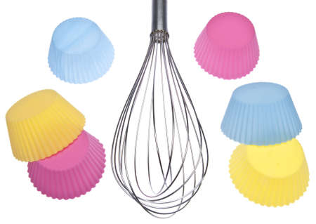 wire whisk: It is time to bake!  Wire whisk with vibrant colored cupcake wrappers isolated on white with a clipping path.