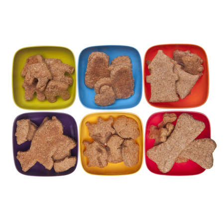 Cookies or pet treats in various shapes displayed in vibrant bowls over white.  photo