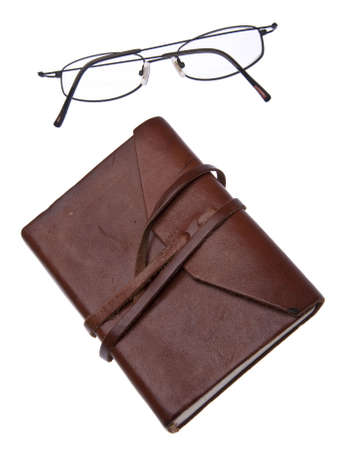 memoir: Old leather journal with simple black glasses