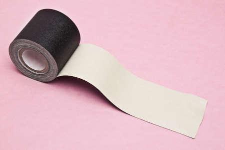 Black gaffers tape on a pink background. Banco de Imagens