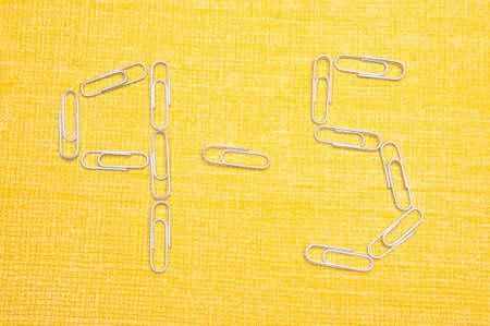 9 5 se exponen en el sujetapapeles sobre un fondo amarillo, un típico día de trabajo.  Foto de archivo - 6680256
