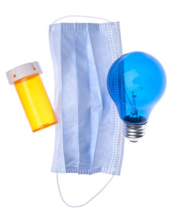 Prescription bottle, surgical mask and light bulb suggest ideas about health care and medicine.