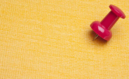 Vibrant Push Pin Marks the Spot on a Yellow Background. Stock Photo