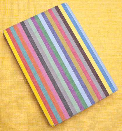 Rainbow striped notebook on a yellow background. Stock Photo