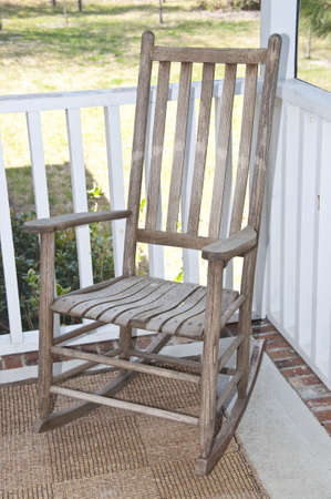 screened: Worn wooden rocking chair on a screened in porch.