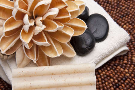 Spa scene with paper lotus flower, massage stones, towel and textured soap.