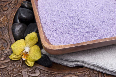 Spa scene with bath salts, massage stones, towel and an orchid on in a carved wood setting. Stock Photo - 6724303