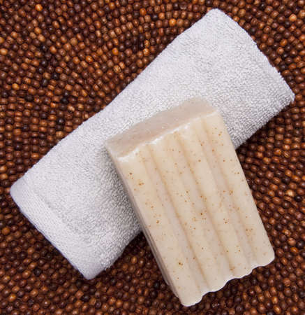 Spa themed image with soap and towel on a dark beaded background.