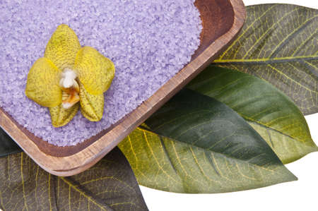Orchid in a bowl of purple bath salts isolated on a leaf background. photo