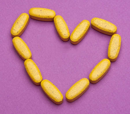 Bright yellow pills in the shape of a heart for a health care concept.