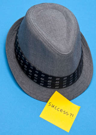 Does Success Make the Man?  Mens hat on blue with Success note. Banco de Imagens