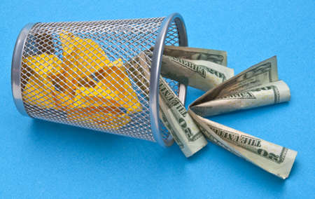 Trash Can with American Money Thrown Away on Blue Background.