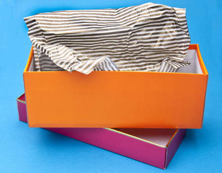 Orange and Pink Fancy Gift Box Opened with Striped Tissue Paper on a Blue Background.