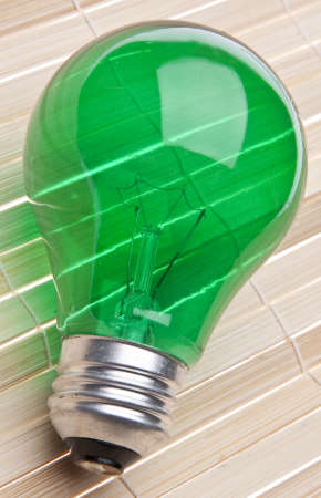 going green: Green Lightbulb on a Bamboo Wood Background Represents Ideas for Going Green.