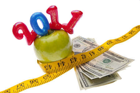 Green Apple with a bright yellow tape measure and money represents the concepts of the cost of diet and healthy lifestyle. Also works for a high cost of healthcare or education concept.  Reklamní fotografie