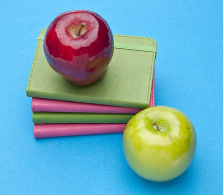 Health Care or Education Themed Image with Books and Apples on a Bright Blue Background. photo