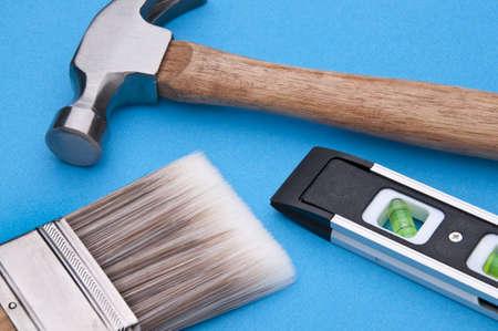 Home Improvement Scene.  Hammer, Level and Paintbrush on Blue. Stock Photo - 6882713
