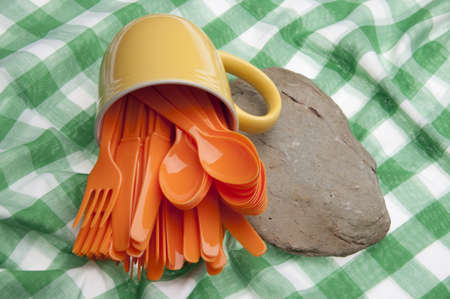 held down: Vibrant Picnic Silverware on a Green Picnic Blanket Held Down by a River Rock. Stock Photo